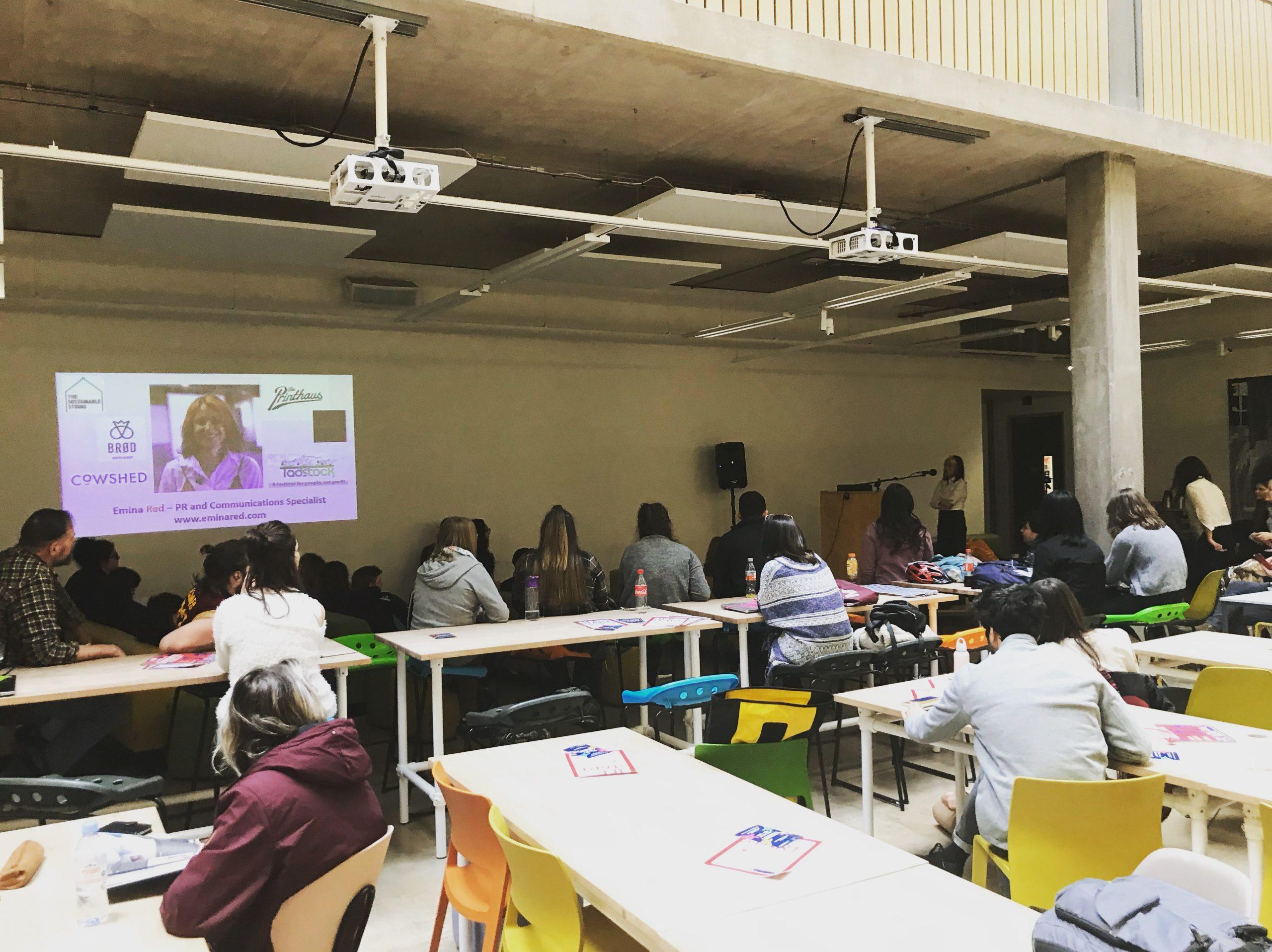 emina speaking in an auditorium to students